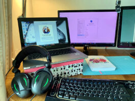 Computer workstation with audio headphones ready for virtual meeting